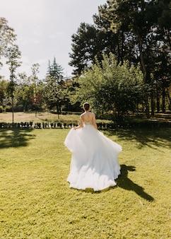 緑の芝生で逃げる長い白いドレスを着た花嫁 Premium写真