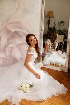 바닥에 앉아 꽃다발과 무성한 드레스 신부