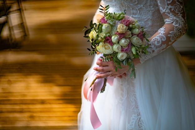 豪華な白いレースのドレスを着た花嫁は、部屋で彼女の手にバラの花束を持っています。閉じる