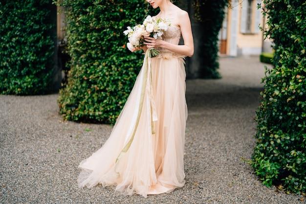 ピンクのドレスを着た花嫁は、絡み合った建物を背景に花束を持っています