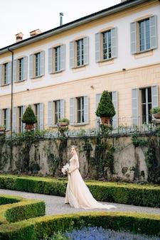 花の花束とピンクのドレスを着た花嫁は、古い別荘の近くの公園を歩きます