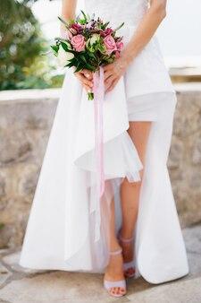 장미 베로니카 가막살 나무속과 웨딩 부케를 들고 열린 다리가있는 세련된 드레스 신부와