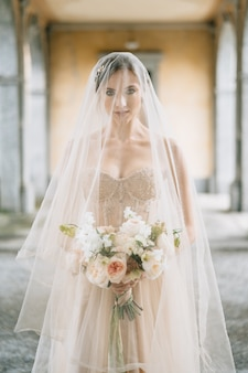 柱のある古いテラスでウェディングドレスと花束のベールの花嫁