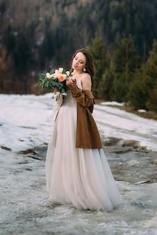 ウェディングドレスの花嫁は花の花束を楽しんでいます。素晴らしい冬の結婚式の写真撮影。
