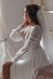 Невеста в свадебном платье в стиле бохо и с фатой позирует, сидя в уютной комнате.