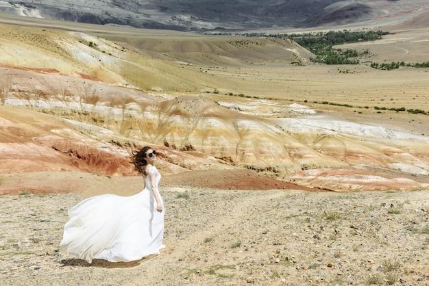선글라스의 아름다운 전망과 함께 산 사막에 웨딩 드레스의 신부
