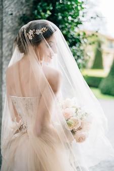 ベールと花の花束を持つウェディングドレスの花嫁は、彼女の頭を近くに向けて立っています