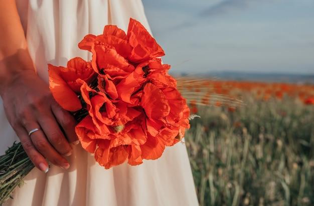 ポピーの花の花束を持っている白いドレスを着た花嫁、赤いポピー畑の暖かい日没時間。スペースをコピーします。