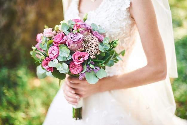 Невеста в белом платье держит букет фиолетовых цветов и зелени