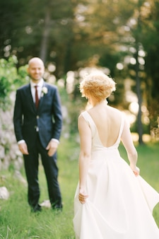 Невеста в белом платье идет навстречу улыбающемуся жениху на фоне зеленых деревьев