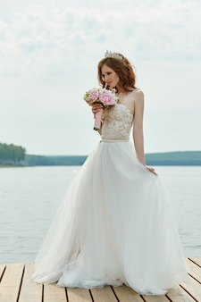 Невеста в белом платье стоит на мосту и смотрит на озеро. женщина в свадебном платье с букетом цветов