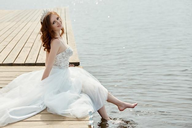 白いドレスを着た花嫁が橋の上に立って湖を見ています。花の花束とウェディングドレスの女性