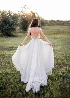 草の上を歩く白いドレスを着た花嫁