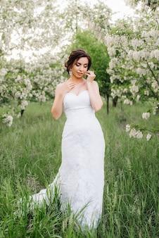 緑の森の大きな春の花束と白いドレスの花嫁