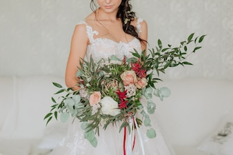 Bride in a white dress with a luxurious bouquet decorated with eucalyptus
