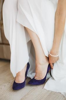 Невеста в белом платье с жемчужным браслетом на руке носит синие туфли на высоком каблуке на ногах.