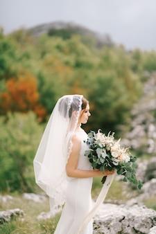 Невеста в белом платье с фатой держит в руках букет цветов на фоне