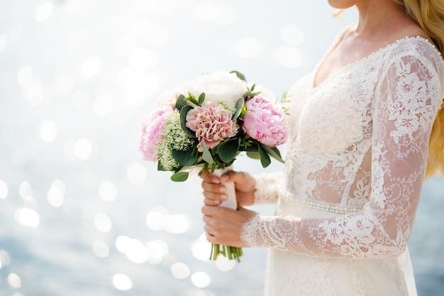 白いレースのドレスの花嫁は彼女の手にピンクの牡丹の花束を持っています