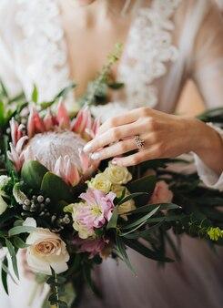 白いウェディングドレスの花嫁は、美しいウェディングブーケの半分の肖像画をストロークします