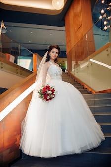 階段の上に立っているエレガントなウェディングドレスの花嫁。女性のための美しいウェディングドレス。花嫁は妻になる準備をしています