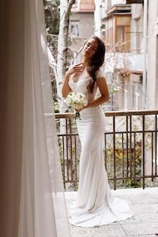 花の花束とエレガントな白いウェディングドレスの花嫁
