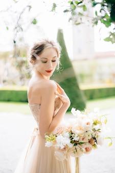 花の花束とオフショルダーのドレスを着た花嫁は、彼女の手を彼女の肩に置き、下げました