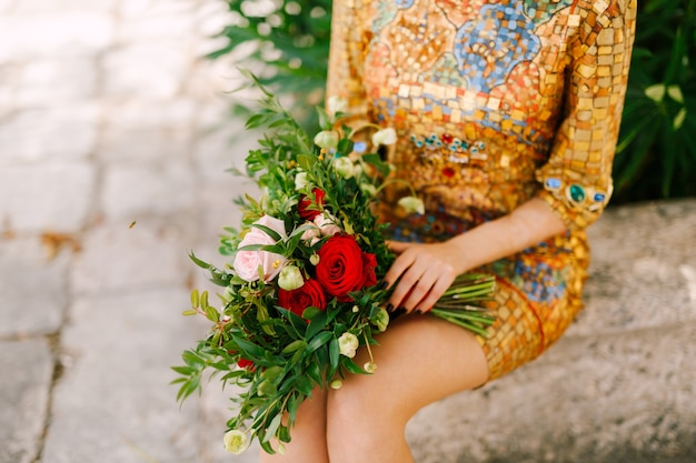 Невеста в необычном золотом платье с иконой сидит и держит букет невесты