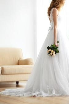 ウェディングブーケを保持している美しいドレスの花嫁