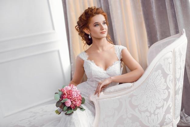 屋内のソファで休んで座っている美しいドレスの花嫁