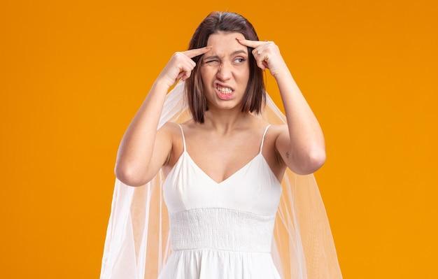 아름다운 웨딩 드레스를 입은 신부는 주황색 위에 서 있는 혼란스럽고 불쾌한 모습을 옆으로 바라보고 있습니다.