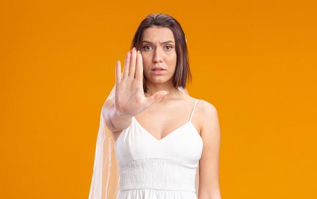 주황색 벽 위에 열린 손으로 정지 제스처를 취하는 심각한 얼굴로 아름다운 웨딩 드레스를 입은 신부