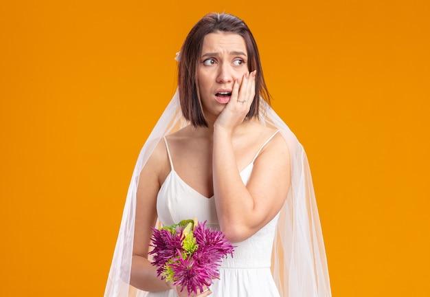混乱して脇を見ている花のウェディングブーケと美しいウェディングドレスの花嫁