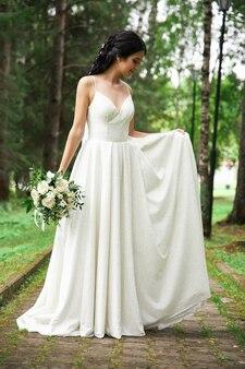Невеста в красивом белом платье и букет цветов в руках