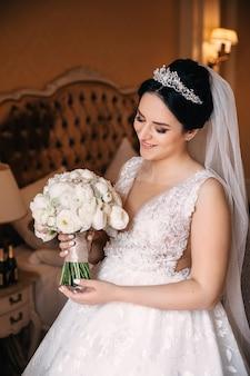 우아한 웨딩 드레스의 신부는 웨딩 부케와 미소를 보유하고 있습니다. 아늑한 침실.