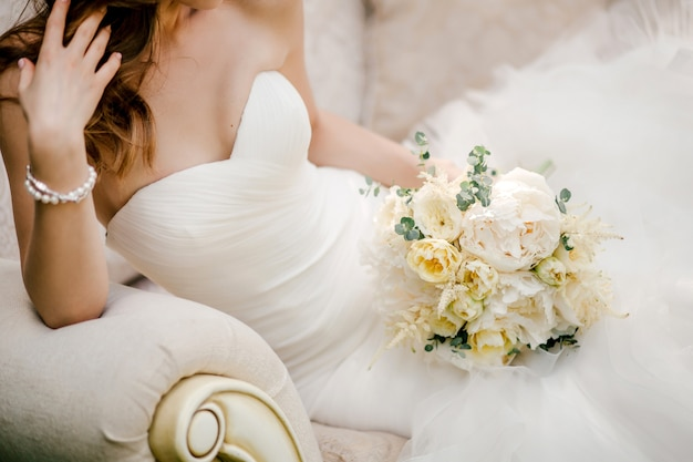 ソファーに座って、ブライダルブーケを持ってエレガントなウェディングドレスの花嫁