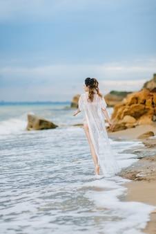 下着姿の花嫁とベールのついたガウンが浜辺を歩く