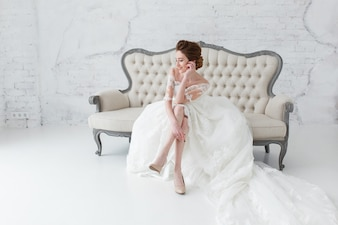 Bride in long dress sitting on sofa indoors in white studio interior like at home.