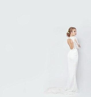 白い背景の上の長い白いウェディングドレスの花嫁。女性の体の豪華なドレス。その少女は結婚の準備をしている。完璧な姿とドレスの女性