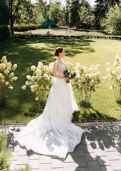 公園に立って、ブライダルブーケを持って長い白いウェディングドレスの花嫁。