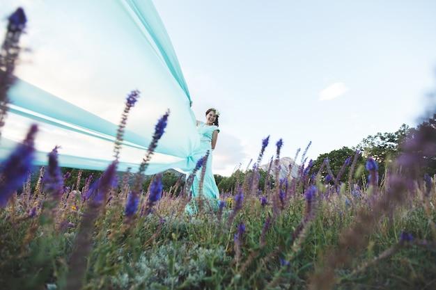 물 근처 산에서 자연의 신부. 드레스 색상 티파니. 신부가 드레스를 가지고 놀아요.