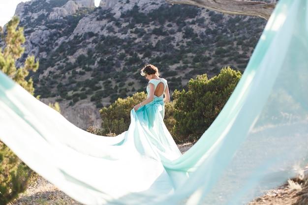 Невеста на природе в горах у воды. цвет платья тиффани. невеста играет с его платьем.
