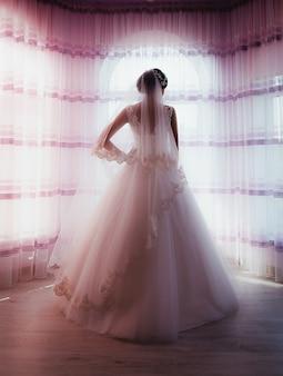 Невеста в платье из пышного тюля и свадебной фате стоит у окна.