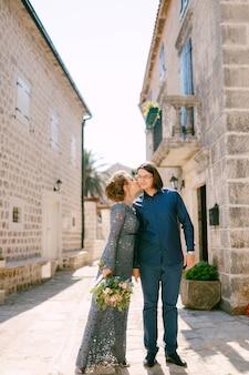 Невеста в стильном синем платье целует жениха на фоне красивых белых домов в