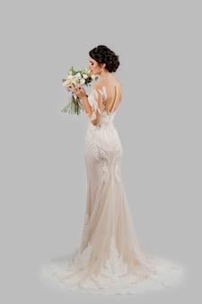Невеста в свадебном платье держит и нюхает букет в студии на пустой стене. портрет привлекательной девушки. вертикальное фото для рекламы в социальных сетях.