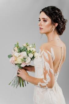 Невеста в свадебном платье держит букет и смотрит налево в студии на глухой стене. портрет привлекательной девушки.