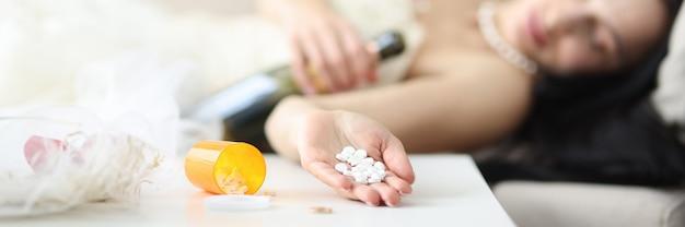 웨딩 드레스의 신부는 그녀의 손 신부 자살 개념에 약을 소파에 누워