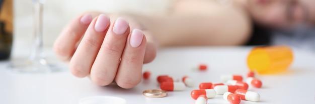 그녀의 손 근접 촬영 자살에 소수의 약으로 소파에 누워 웨딩 드레스의 신부
