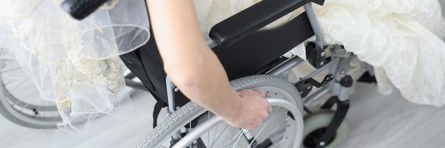 ウェディングドレスの花嫁は、障害を持つ人々の概念の車椅子の家族生活に座っています