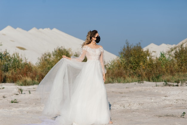 Невеста в свадебном платье с медицинской маской в период карантина по коронавирусу covid-19.