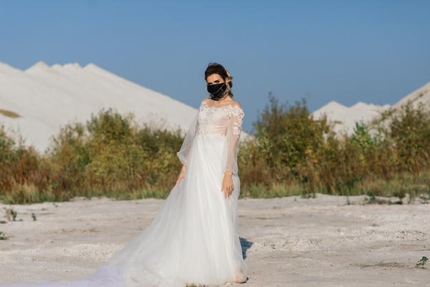 コロナウイルスcovid-19検疫期間で医療マスク付きのウェディングドレスの花嫁。